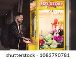 Small photo of KRAKOW / POLAND - 05.02.2018: Young hipster man with a beard in black jacket and with backpack playing in a vending machine pullout soft toys. Strong an with beard playing in toys machine and smiling.