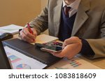 Small photo of Business man doing finances on calculate analysis working with financial results Financial accounting sales forecast graph. Businessman Calculating Invoices Using Calculator