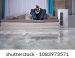 upset  man on sofa with hands... | Shutterstock . vector #1083973571