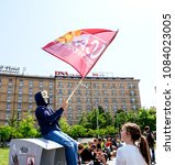 Small photo of STRASBOURG, FRANCE - MAY 5, 2018: People making a party protest Fete a Macron in front of Gare de Strasbourg - young boy with anonymous mask waving communist flag