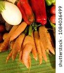 Small photo of Berenjena blanca, pimientos rojos brillantes y entreverados, manojo zanahorias con raíz y efecto dedos. Mantel verde. Puesto de verduras, cultivo ecológico.