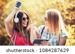 listening to music. two smiling ... | Shutterstock . vector #1084287629
