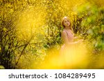 Small photo of Beautiful woman, dressed in a chacked top and skirt, standing between branches of yellow blossom tree