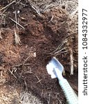 Small photo of Small silver shovel delve rich nutrient soil, for planting. The soil contains hay and dry leaf.