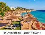 sunny resort beach with palm... | Shutterstock . vector #1084456244