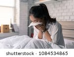 Small photo of The businessman is unable to work, she is sick and sneezing heavily in bed.