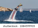 Small photo of Palma de Mallorca, Spain - August 21, 2013: A man practices flyboard in the beach of palmanova an aquatic modality adding a water jet push system to a board to create up to 8 meters jumps over the sea