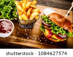 tasty burger with chips served... | Shutterstock . vector #1084627574