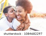 Happy young mother having fun with her child in summer sunny day - Son kissing his mum outdoor with back sun light - Family lifestyle, motherhood, love and tender moments concept - Focus on woman face