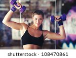 Young strong woman with dumbbells. - stock photo
