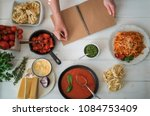 opened recipe book in the hands ...   Shutterstock . vector #1084753409