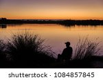 Silhouette Of Man Fishing At...