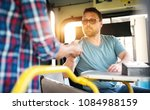 young bus driver is handing out ... | Shutterstock . vector #1084988159
