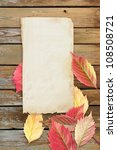 Autumn leaves and old paper on the table - stock photo