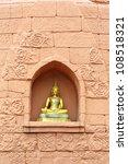 Buddha statue on brick wall - stock photo