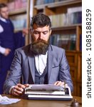 Small photo of Man with beard and busy face sit in library and work with typewriter, close up. Writers routine concept. Author types novel or poem. Writer working on new book with bookshelves on background.