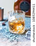 Small photo of Glass of scotch whiskey with ice cubes, bottle and copper bar accessories