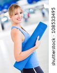Fit woman at the gym holding a yoga mat - stock photo