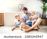 father with two toddlers... | Shutterstock . vector #1085343947