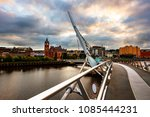 Derry, Northern Ireland. Peace bridge in Derry Londonderry in Northern Ireland, UK with city center at the background. Sunny evening with cloudy sky, reflection in the river
