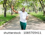 Small photo of Friendly sporty black guy jogging in city park and greeting familiar sportsmen. Young Afro American man running outdoors and waving hand. Sport and communication concept
