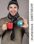 Small photo of Male person drinking coffee and use blue toy.