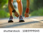 woman runner tying shoelace... | Shutterstock . vector #1085999045