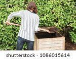 woman tumbling the compost with ... | Shutterstock . vector #1086015614