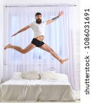Small photo of Man in shirt and underpants jumping on bed, white curtains on background. Macho with beard jumps high in air. Full of strength and energy concept. Guy on cheerful face full of energy in morning.