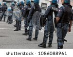 Small photo of MILAN, iTALY - MAY 5, 2018: Riot police in full tactical gear stand ready to confront anarchic activists during a demonstration in the city streets.