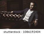 imposing young man sitting on a ... | Shutterstock . vector #1086192404