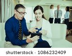 Small photo of Senior businessman showing something on tablet to young female colleague. They are discussing something and sitting on sofa in office. There are three colleagues standing in background and talking.