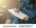 young woman writing into her... | Shutterstock . vector #1086288527
