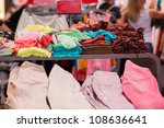 Variety of color t-shirts and jeans on table in mall - stock photo