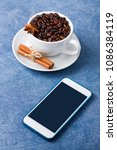 Small photo of Mobile phone mockup on blue table and cup of coffee wit seeds, cinnamon and anis. Vertical orientation, place for copy space, close up.