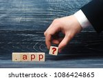 Small photo of A man's hand in a suit holds out a square with a question mark to the inscription of the App. A domain of high level, the sale of domains for Web sites and services. New domain on the Internet