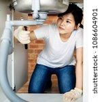 asian woman fixing kitchen sink | Shutterstock . vector #1086604901