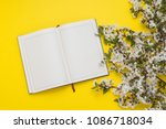 Diary and Cherry Twig with Flowers on a Yellow Background.