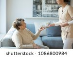 friendly caregiver giving a cup ... | Shutterstock . vector #1086800984