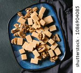 Small photo of Salted caramel fudge candy served on blue ceramic plate with caramelized walnuts on textile napkin over black texture background. Top view, space. Dessert set. Square image