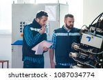 The engineer and the worker are examining the machine - stock photo