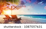 Two Deckchairs Under Parasol I...