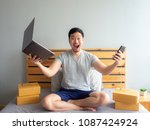Small photo of Surprise and shock face of Asian man success on making big sale of his online store. Concept of freelance startup and online business home office.