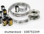 Black and white 35mm film cartridge and reel - stock photo