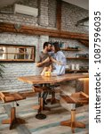 Small photo of Young affectionate couple enjoying coffee and fruits in the kitchen