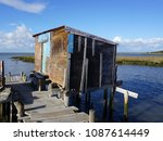 old wooden house in river   | Shutterstock . vector #1087614449