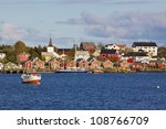 Picturesque town of Reine on Lofoten islands in Norway with fishing boats and typical red rorbu houses by the fjord - stock photo