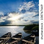 sunset over river with boats - stock photo