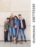 Small photo of Happy affectionate family with two young boys and their dog posing arm in arm in front of a commercial building smiling at the camera
