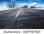 empty winter countryside road... | Shutterstock . vector #1087987565